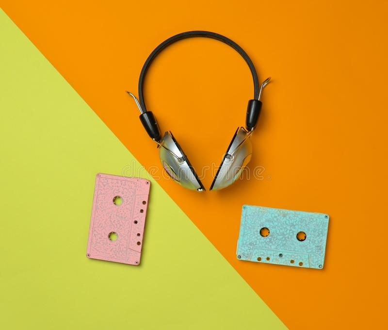 Wireless headphones and audio cassettes. On a multicolored pastel paper background. Minimal creative art. Musical retro vibrations. Top view stock photo
