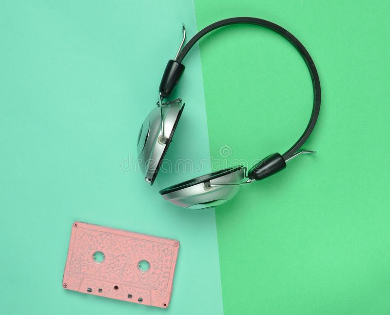 Wireless headphones and audio cassettes. On a multicolored pastel paper background. Minimal creative art. Musical retro vibrations. Top view stock photos