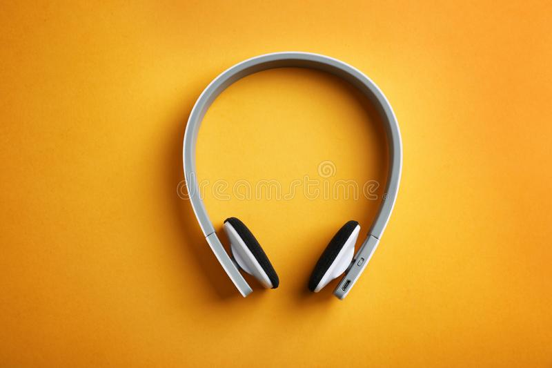 Wireless headphones on color background. Top view stock image