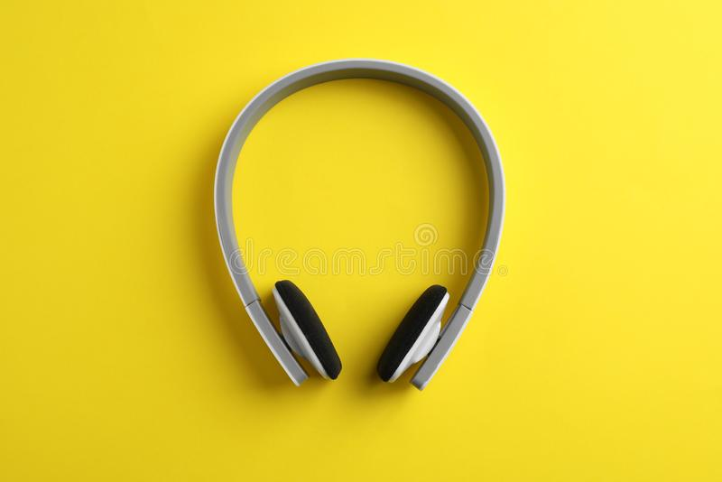 Wireless headphones on color background. Top view stock photography