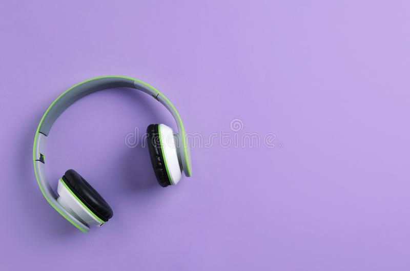 Wireless headphones on color background, top view. Space for text stock photography