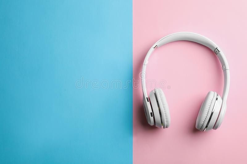 Wireless headphones on color background, top view. Space for text royalty free stock photography