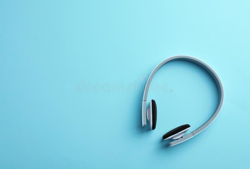 Wireless headphones on color background, top view. Space for text royalty free stock images