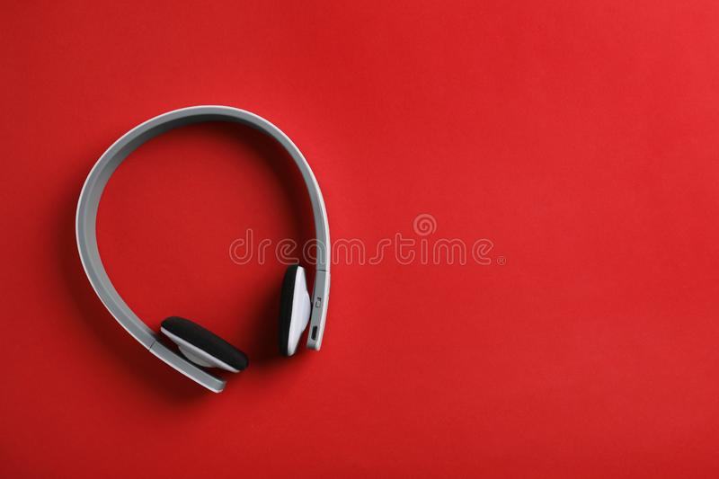 Wireless headphones on color background, top view. Space for text stock image