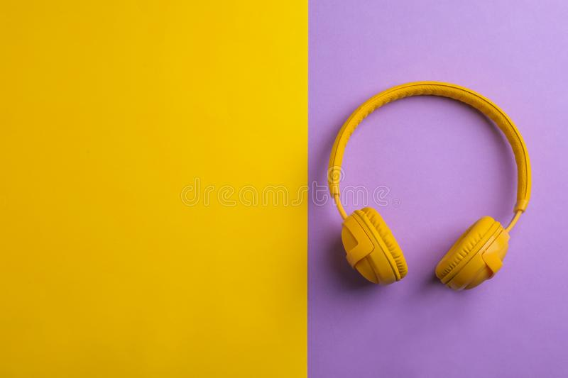 Wireless headphones on color background. Top view. Space for text stock photo