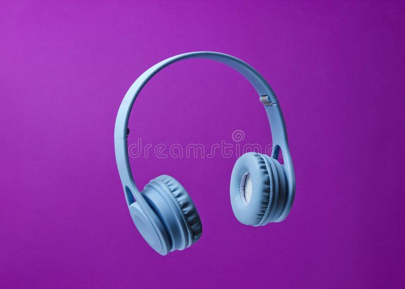 Wireless headphones. 3D surround photo blue wireless headphones on a purple background royalty free stock photos