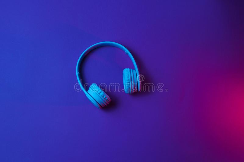 Wireless headphones. On dark blue red background. Neon light. Top view royalty free stock photo