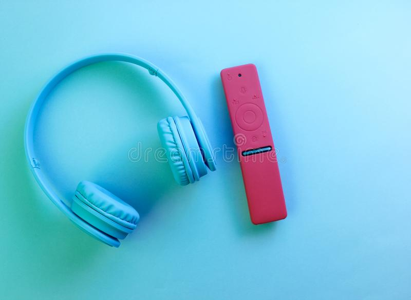 Wireless headphones, modern TV remote. Neon blue light. Home relaxation concept. Top view stock photos