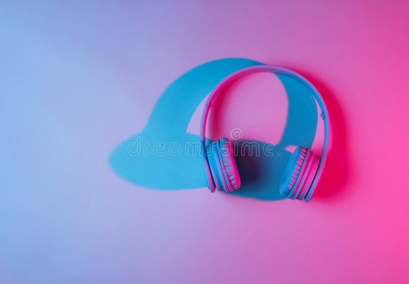 Wireless headphones. Retro wave, neon light, ultraviolet. Top view, minimalism royalty free stock image