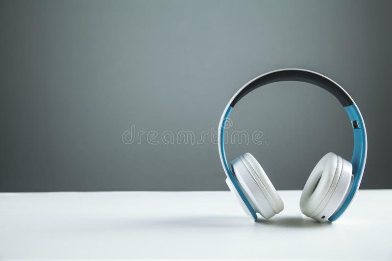 Wireless headphones on white desk royalty free stock photos