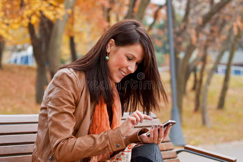 Wireless internet fun. Beautiful young woman has fun using mobile wireless internet device. Selective focus and beautiful autumn colors in background