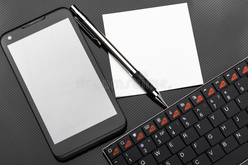 Wireless keyboard, smartphone with blank screen, pen and stickers on dark background. stock images