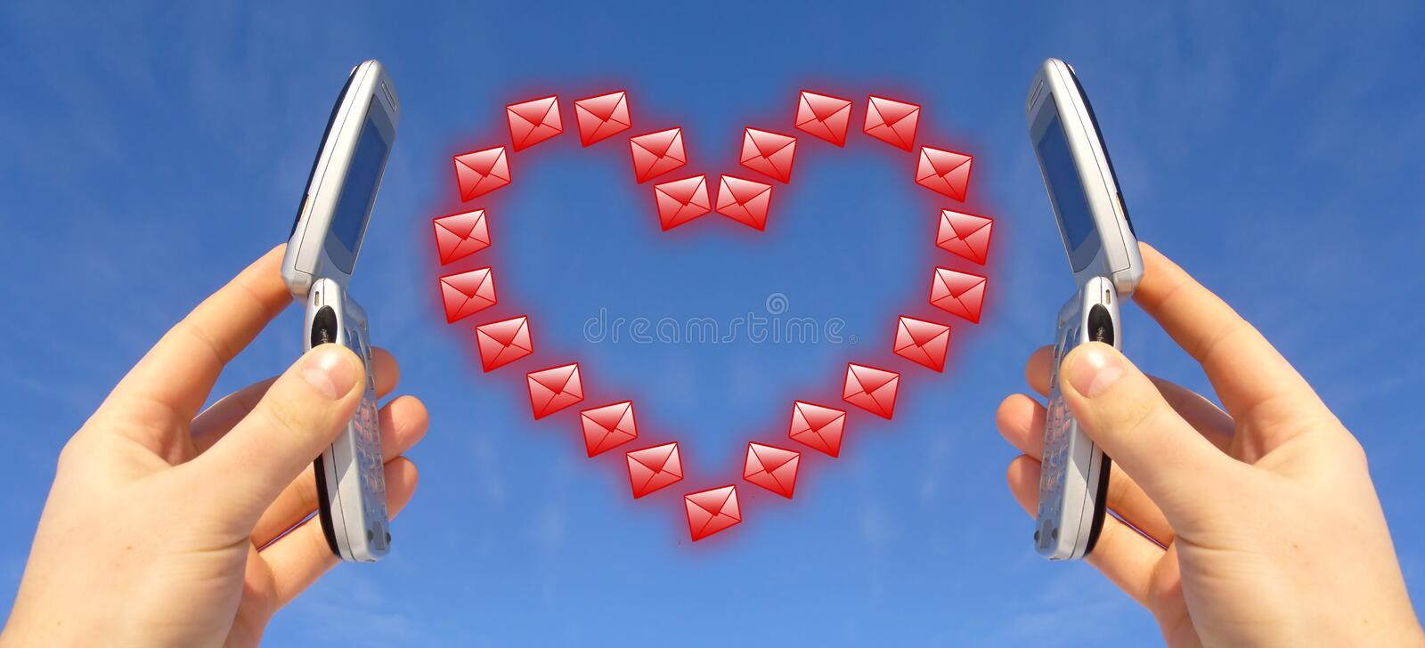 Wireless Love Connection. Two wireless cellphones held against a blue background with a red heart made of small envelopes symbolizing messages of love shared by stock photo