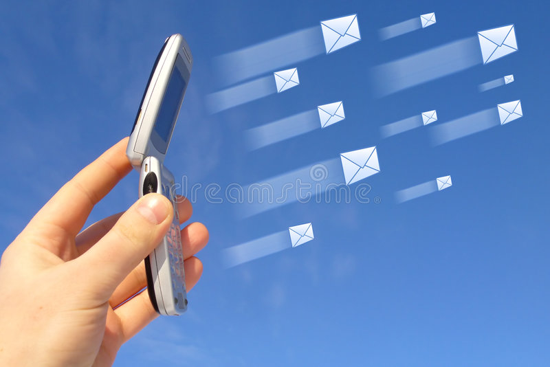 Wireless Messaging. An open cellphone is held against the blue sky or background by a raised hand with several white envelopes of various sizes appear to fly royalty free stock photography