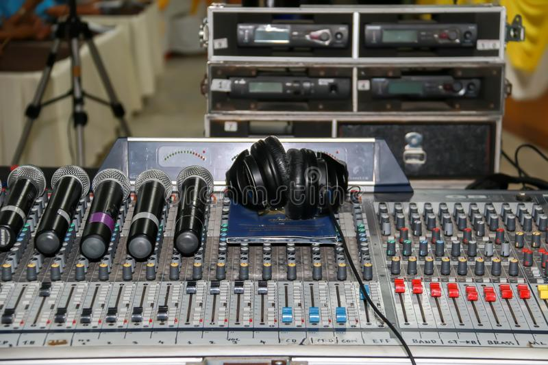 Wireless microphone and headphone put on sound music mixer control panel. Sound Mixer Equalizer Panel royalty free stock photos