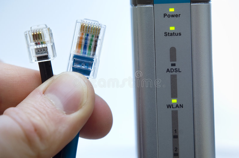 Wireless Networking and Security. Networking and security concepts. Hand holding a network and telephone cable with ADSL wireless router