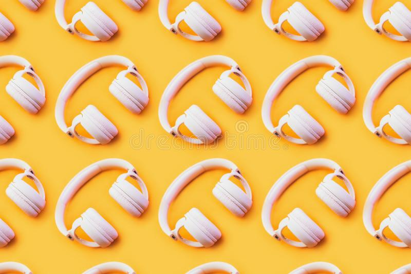 Wireless pink headphones on an yellow background. stock image
