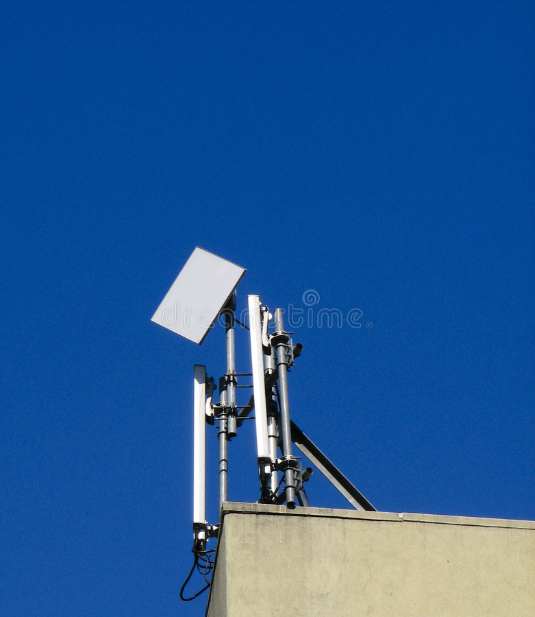 Wireless radio antenna. On top of building royalty free stock photo