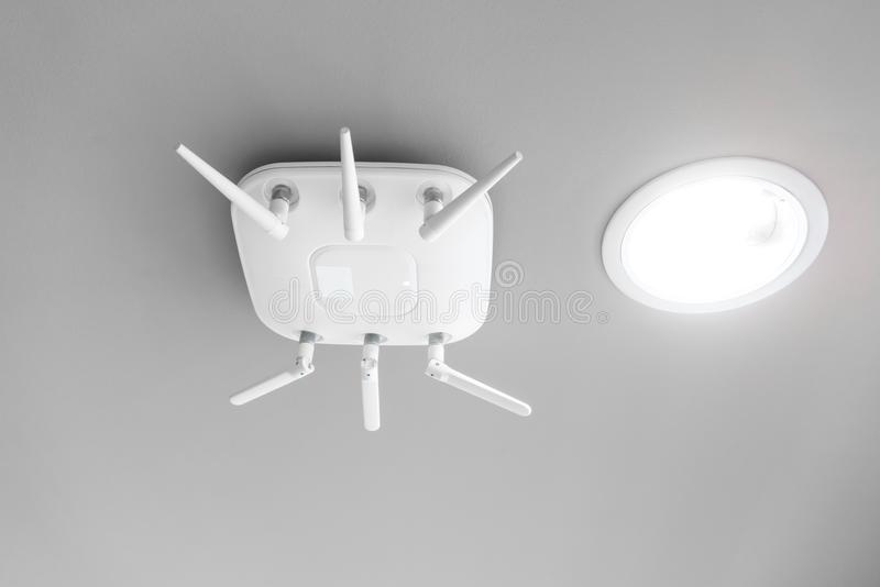 Wireless router for network hanging on white ceiling. stock photography