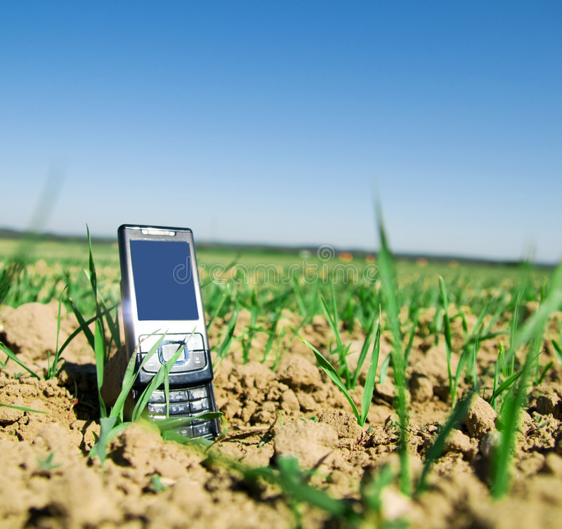 Wireless technology. Two mobile phones on the field. Wireless technology, communication concepts royalty free stock photography