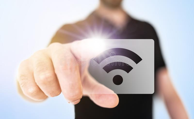 Wireless technology concept with man touching wifi icon on translucent screen interface stock photography