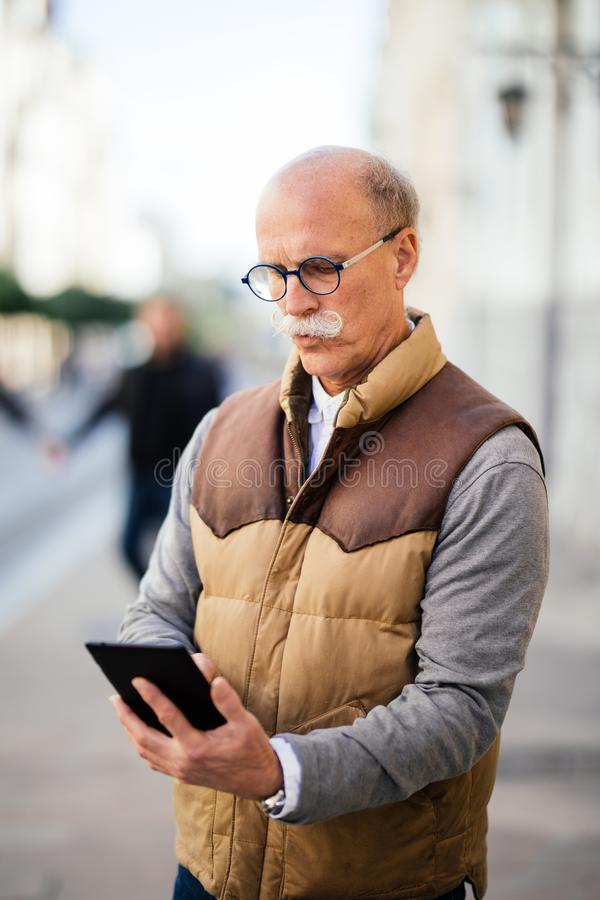 Wireless technology keeps my daily tasks streamlined. Shot of a senior man sitting outdoors and looking at his tablet. royalty free stock photography