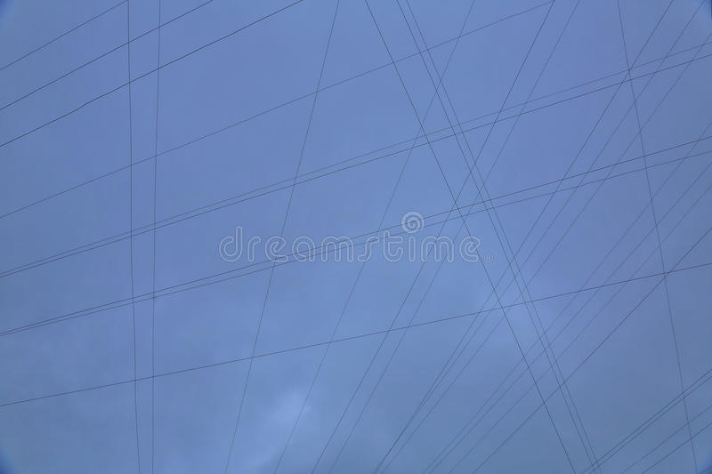 The wires on the cloudy sky background. Symmetrical pattern of electrical wires on the cloudy sky background stock photo