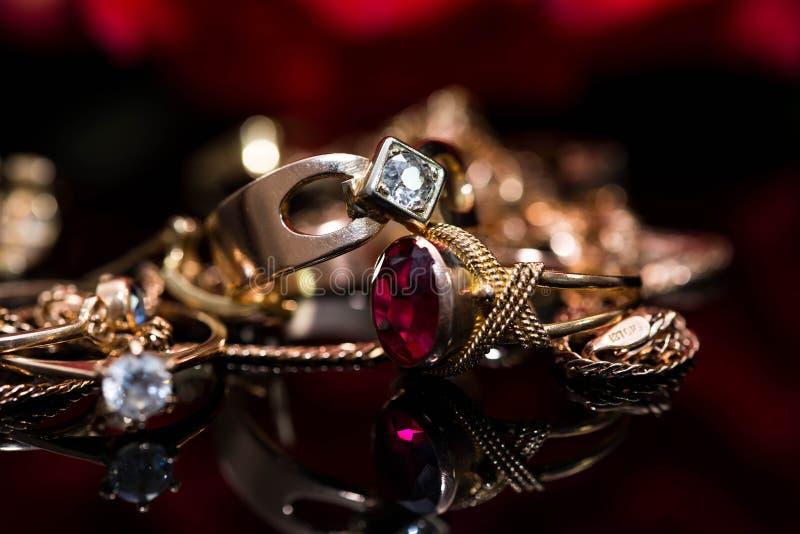 Wirkliche Goldringe mit Diamanten, Kettenabschluß herauf Makroschuß auf dem Reflektieren der schwarzen glänzenden Oberfläche lizenzfreie stockbilder