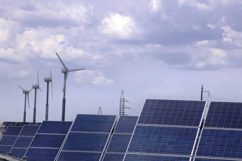 Wirkliche Sonnenkollektoren und Windmühle stockfotografie