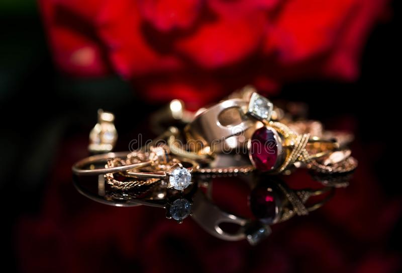 Wirklicher Goldring mit Diamanten, Kettenabschluß herauf Makroschuß auf dem Reflektieren der schwarzen glänzenden Oberfläche stockfotografie