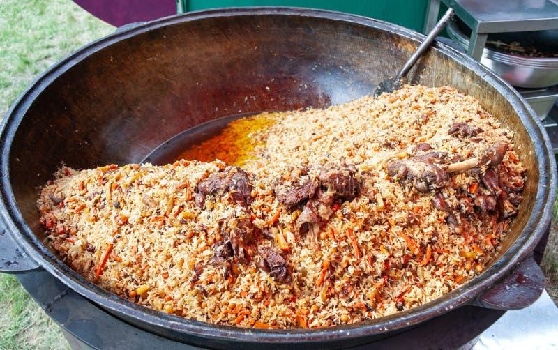 Wirklicher Pilaf in einem enormen großen Kessel Kochen von Nationalgerichten Traditionelles Pilafkochen stockbild
