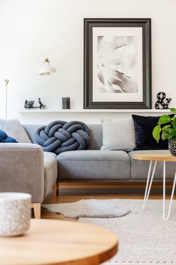 Wirkliches Foto des handgemachten Knotenkissens gelegt auf das graue Ecksofa, das in weißen Wohnzimmerinnenraum mit Lampe, Dekor  lizenzfreies stockfoto
