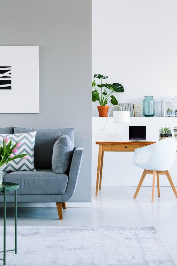 Wirkliches Foto des modernen flachen Innenraums mit grauer Couch, hölzerner Schreibtisch lizenzfreies stockfoto