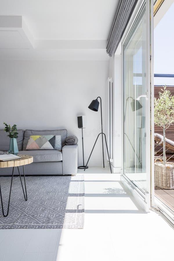 Wirkliches Foto des weißen Wohnzimmerinnenraums mit grauer Couch, schwarz stockfoto