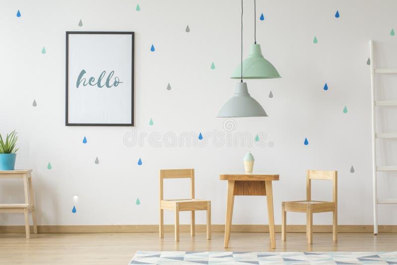 Wirkliches Foto einer grünen und grauen Lampe, die über einem Holztisch hängt lizenzfreies stockfoto