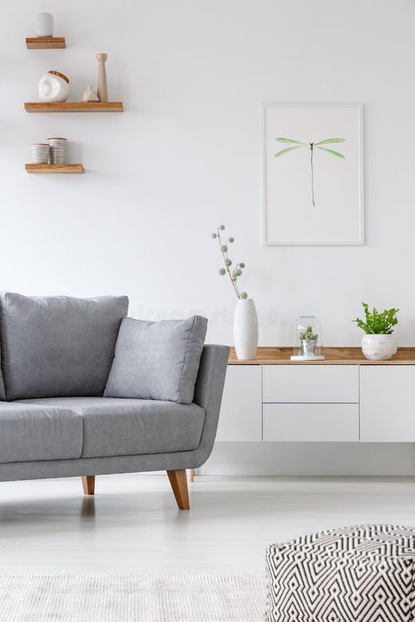 Wirkliches Foto einer grauen Couch, die nahe bei einem Schrank mit Vase steht stockfotos