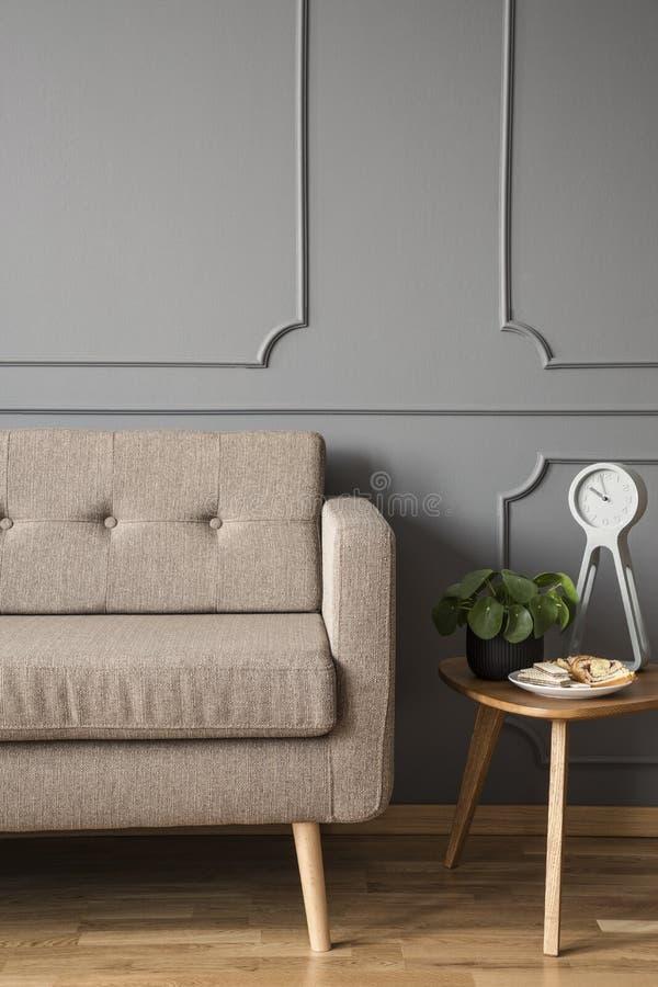 Wirkliches Foto einer Retro- Couch, die nahe bei einer kleinen Tabelle mit steht lizenzfreie stockfotografie