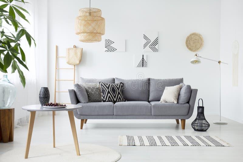 Wirkliches Foto eines einfachen Wohnzimmerinnenraums mit Kissen auf gra stockfoto