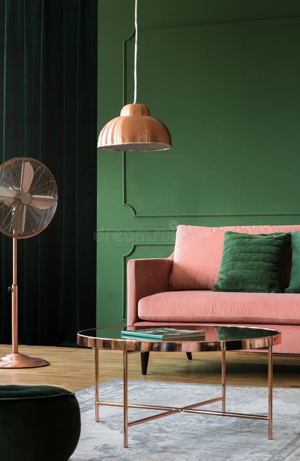 Wirkliches Foto eines kupfernen Couchtischs, der Lampe und des Fans nahe bei einem rosa Sofa des Pulvers in einem Wohnzimmerinnen stockbild