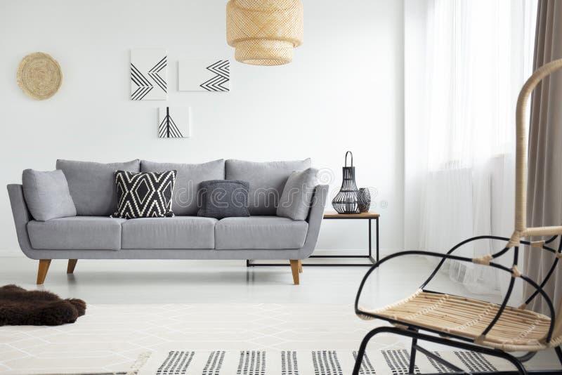 Wirkliches Foto eines Rattansessels gegenüber von einem grauen Sofa im scandi lizenzfreie stockbilder