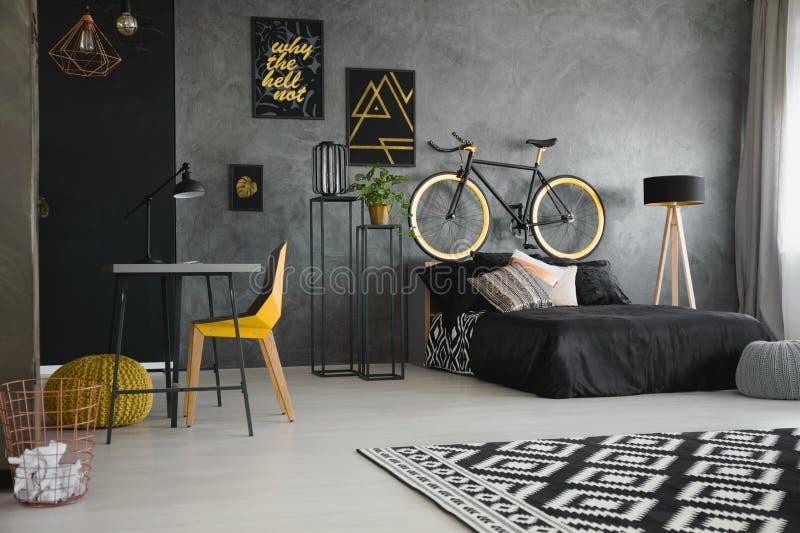 Wirkliches Foto eines schwarzen Betts, das gegen rohe, graue Wand in Umb. steht stockfoto