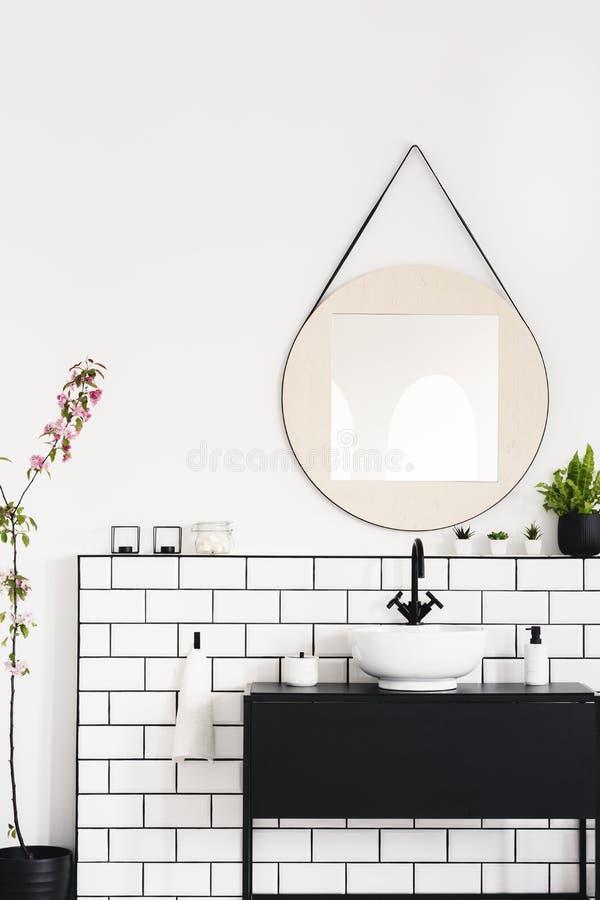Wirkliches Foto eines schwarzen Schranks, des runden Spiegels und der weißen Fliesen in einem modernen Badezimmerinnenraum stockfotos