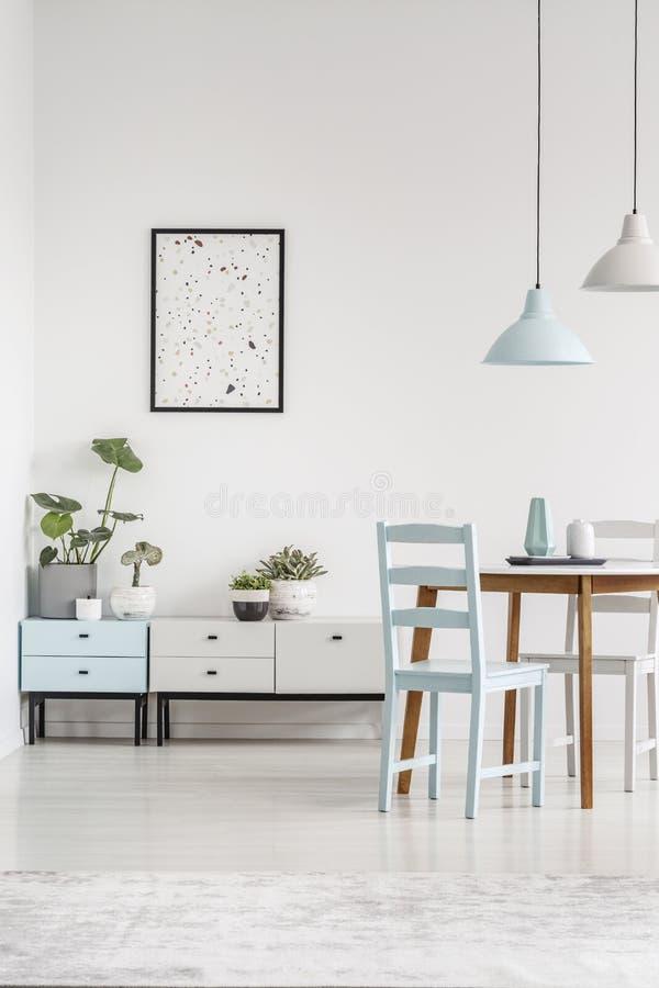Wirkliches Foto von niedrigen Kabinetten, Grafik auf der Wand und Speisetisch stockfotos