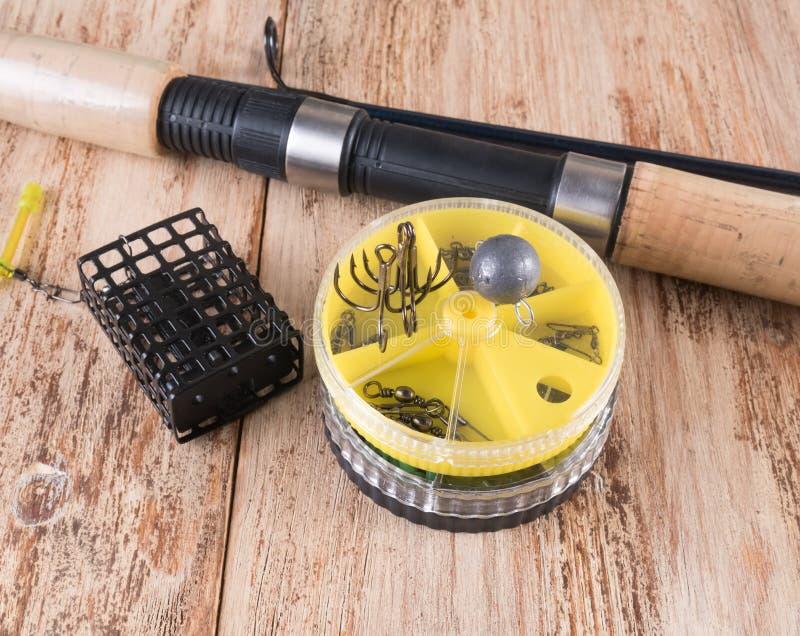Wirować, czarna synklina, round pudełka, haczyki i sinkers na drewnianym tle, zdjęcie royalty free