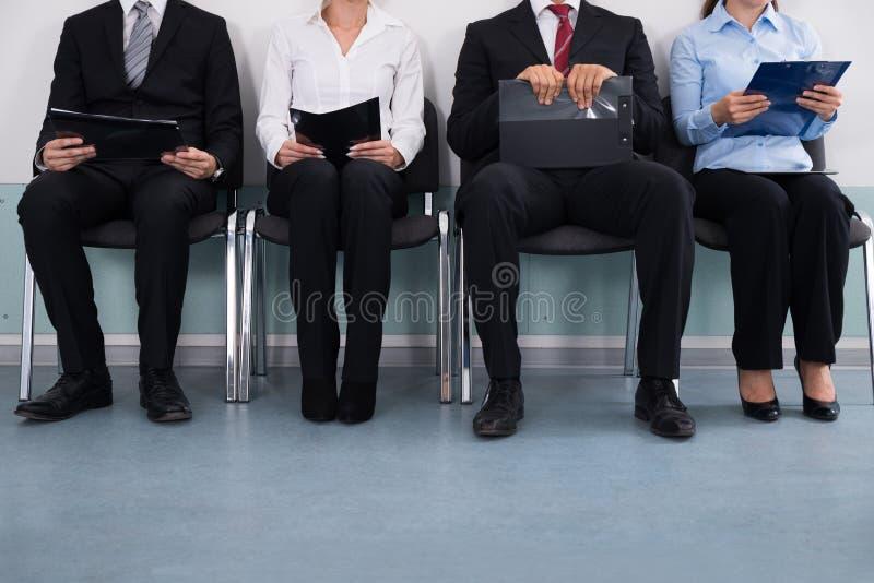 Wirtschaftler, die auf Stuhl sitzen stockfotos