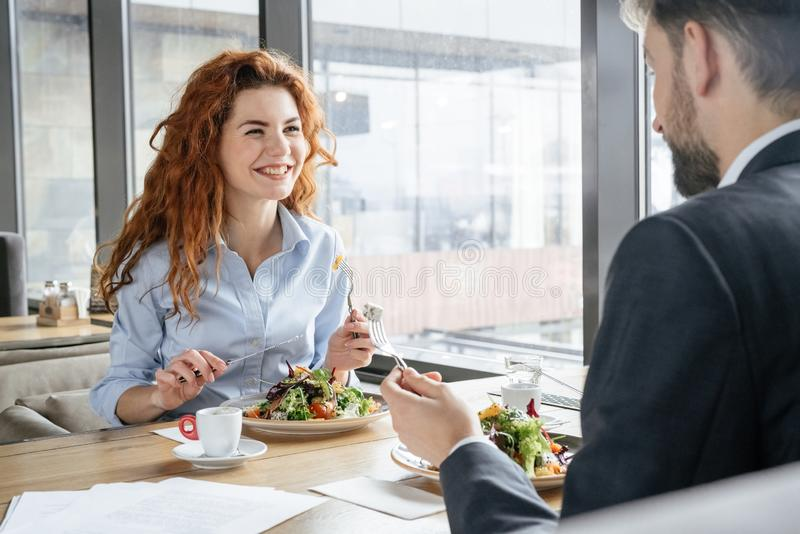 Wirtschaftler, die Business-Lunch des Essensalats des Restaurants in der sitzenden trinkenden Espressounterhaltung nett zu Mittag stockfotos