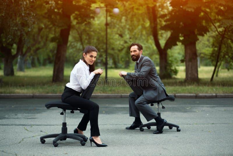 Wirtschaftler, die das Laufen auf Bürostühlen haben stockbilder