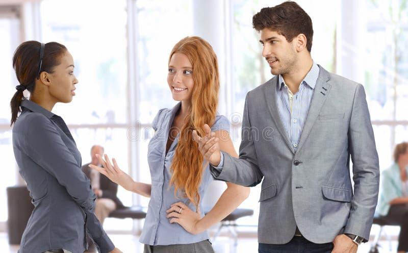 Wirtschaftler, die an der Bürolobby sprechen stockfoto