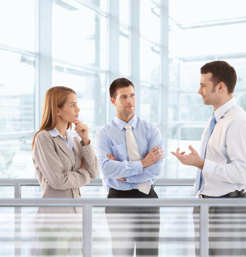 Wirtschaftler, die in der modernen Bürovorhalle plaudern lizenzfreie stockfotos