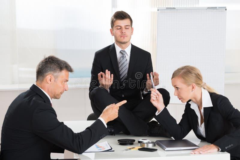 Wirtschaftler, die in Front Of Businessman Meditating streiten stockbilder